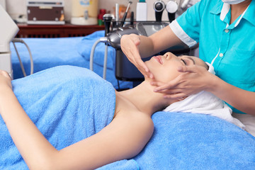 Young Asian woman in towel enjoying face massage in spa salon with professional master