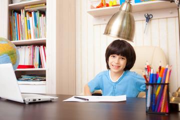 smiling schoolboy doing homework