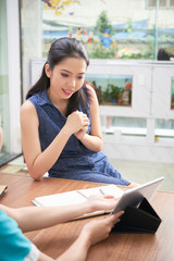 Charming Asian woman visiting spa salon and watching tablet at registration stand