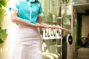 Faceless shot of woman welcoming guests in spa salon standing near glass doorway