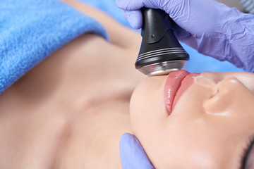 Closeup shot of specialist doing face procedure with electronic instrument to young client in salon