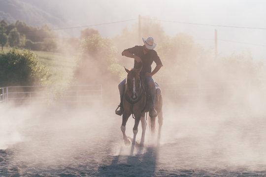 Cowboy horse riding in dusty equestrian arena, Primaluna, Trentino-Alto Adige, Italy