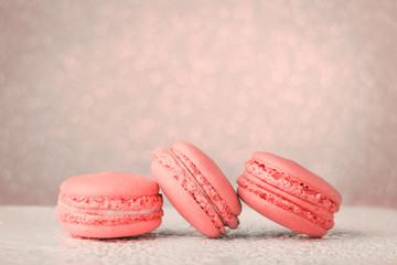 Macarons toned in Living Coral color of the Year 2019. Color palette, glitter bokeh background, copy space.
