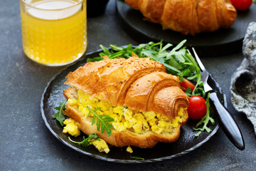 Breakfast of croissant with scrambled eggs and salad.