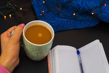 Cup of coffee in hand and a notebook on the table. new year mood