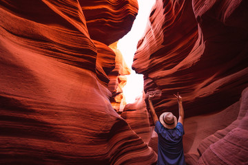 USA, Arizona, tourist making victory sign in Lower Antelope Canyon