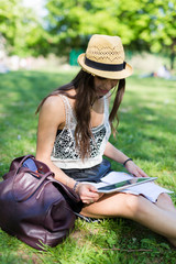 Young student sitting on a meadow in a park using digital tablet