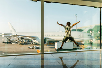 Spain, Barcelona airport, Boy in departure area, jumping in front of glass pane