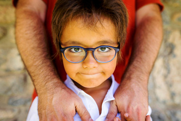 Portrait of little boy wearing glasses standing in front of his father