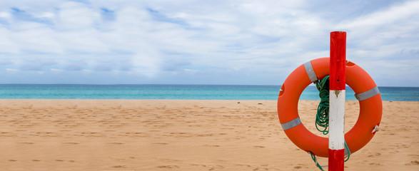 Life preserver on sandy beach, Life belt on the beach