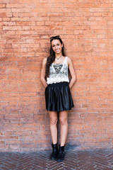 Portrait of fashionable young woman standing in front of brick wall