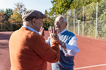 Two fit seniors high fiving on a basketball field