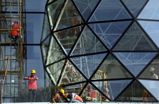 Construction workers install glass on the exterior of Gulita, a bungalow which according to local media will be the marital home of Isha Ambani, daughter of the Chairman of Reliance Industries Mukesh Ambani, in Mumbai