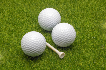 Close up view golf balls and tee on grass background.