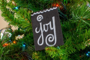 A wooden ornament with the word 'Joy' Hangs on a light christmas tree