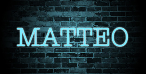 first name Matteo in blue neon on brick wall