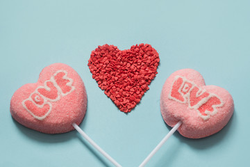 Couple valentine lollipops pink pops on pastel blue. Funny concept. Copy space. Close up.