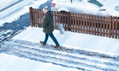 Mann räumt Schnee im Winter, Winterdienst, Wintereinbruch