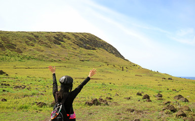 Female tourist raising arms excited to visit Rano Raraku volcano, quarry of the famous Moai statue on Easter Island of Chile