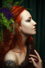 Young red head model is posing with a creative makeup