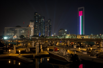 Foto op Canvas Las Vegas Beautiful view of Abu Dhabi city famous landscape displaying UAE flag, Etihad towers and Marina boats at night