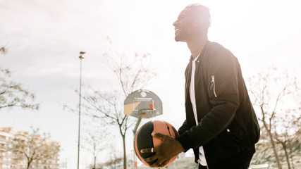 Side view of young african man throwing a ball in a basket on a basketball court
