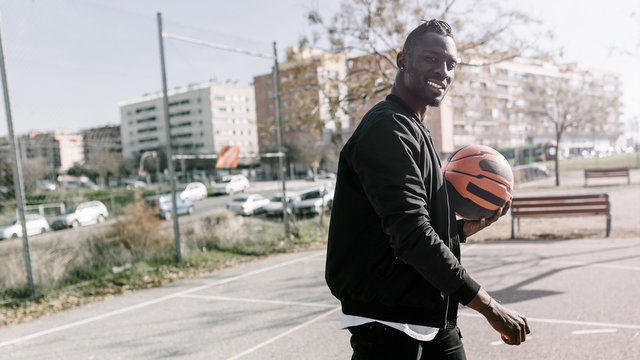 Side view of young african man smiling and holding a ball in a basket on a basketball court