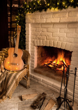 Burning fireplace decorated with Christmas garland. Near the wicker chair with a guitar and a rug.