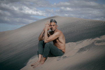 Man sitting on sand dunes