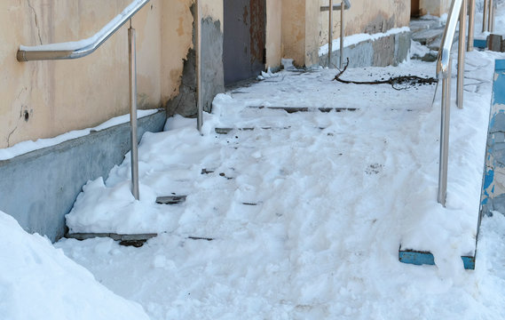 Snowy slippery stairs of the porch in winter day.