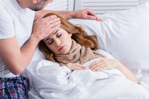 . husband touching forehead of sick wife with fever in bed  Stock