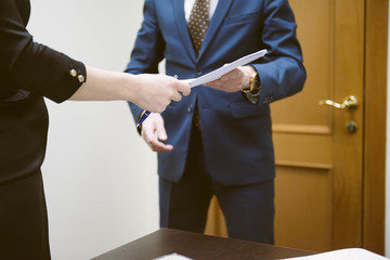 Conclude a contract. Business man and business woman sign a contract in the office. Businesswoman gives contract.