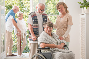 Group of positive senor friends with their caregiver in nursing home for elderly
