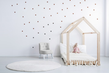 Pastel grey armchair next to wooden house shape bed with toy and blanket, copy space and golden stars on empty white wall, round white carpet on floor