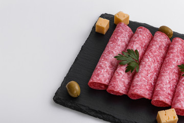 delicious sliced salami on a stone plate white background