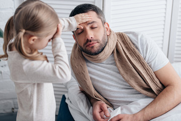 daughter touching her and sick father foreheads and checking temperature in bedroom