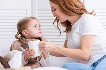 mother taking care of sick daughter and giving her cup of tea in bedroom