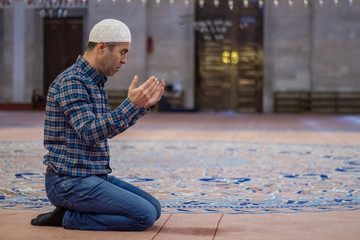 Young adult caucasian man to praying at the mosque