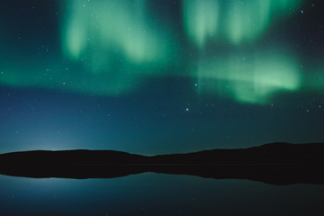Northern lights and stars on the night sky near lake with calm water. Murmansk region, Russia