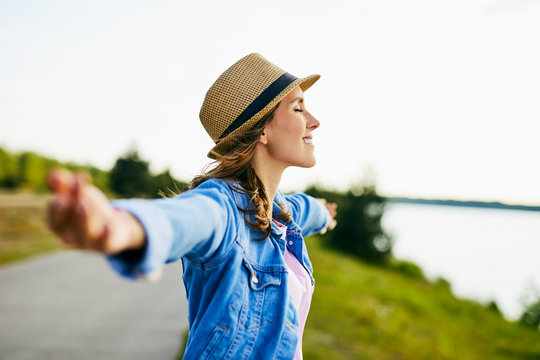 Portrait of young woman stretching her arms with eyes closed enjoying beautiful summer day