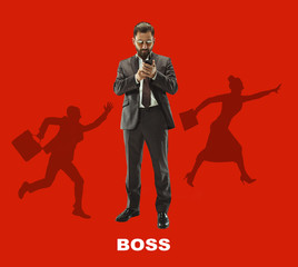 Handsome businessman with mobile phone. Serious business man standing isolated on red background. Boss concept