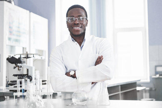 The scientist works with a microscope in a laboratory conducting experiments and formulas.