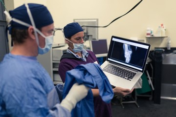 Female nurse showing x-ray report to male surgeon on laptop