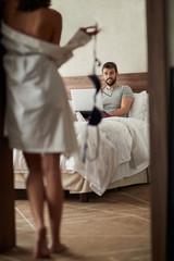 woman seduces her boyfriend in the bedroom.
