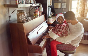 father with child girl on Christmas play music on piano. concept of holidays and family happiness..