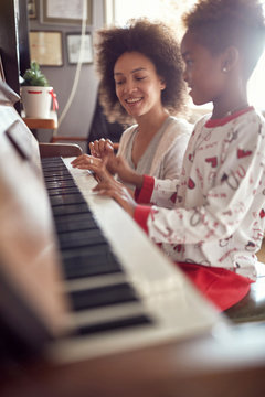 mother with child on Christmas play music on piano. concept of holidays and family happiness..