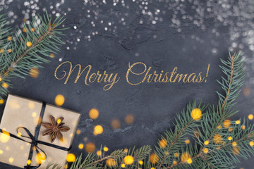 Merry Christmas card with golden text, gift with anise star, fir branches, snowflakes and lights on gray concrete background. Greeting card concept, top view, flat lay, layout design