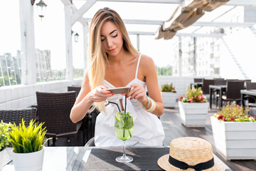 A girl in a white dress. In summer, a bright sunny day in a cafe on veranda. Photograph on phone a glass of soft drinks. Post in social networks. Photos for Internet. Tanned skin has long hair.