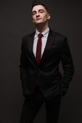 young man in elegant suit posing. Business style. Male beauty, fashion. Hairstyle.