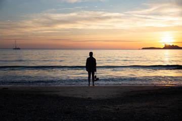 Femme sur la plage regardant le coucher du soleil